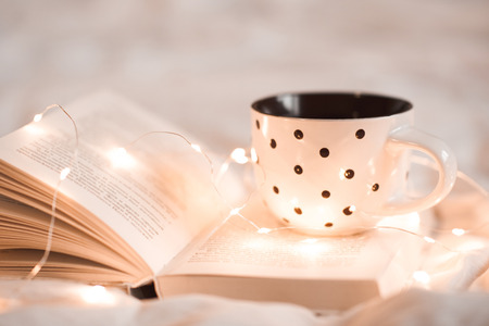 Cup of tea staying on open book with Christmas lights in bed closeup. Good morning. Breakfast time.  Stock Photo