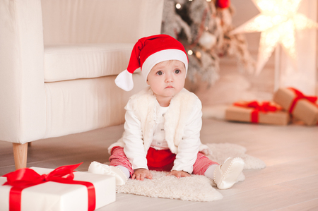 Sad baby girl 1 year old wearng santa claus hat sitting on floor over Christmas background in room. Open presents. Holiday season.