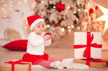 部屋のクリスマスツリーの上にクリスマスプレゼントと床に座ってかわいい女の子の女の子の年。ホリデーシーズン。小児。