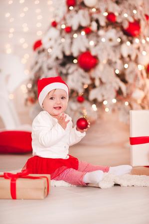 ハッピー ベビー女の子 1 歳の部屋でクリスマス背景の上の床に座ってクリスマス ボールを保持しています。カメラを見ています。ホリデー シーズ