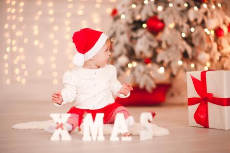 部屋に白い木製のクリスマスの手紙で床に座っているサンタクロースを身に着けているかわいい女の子。目をそらす。ホリデーシーズン。