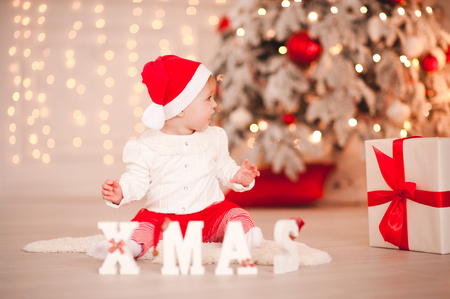Cute baby girl wearing santa claus sitting on floor with white wooden xmas letters in room. Looking away. Holiday season.