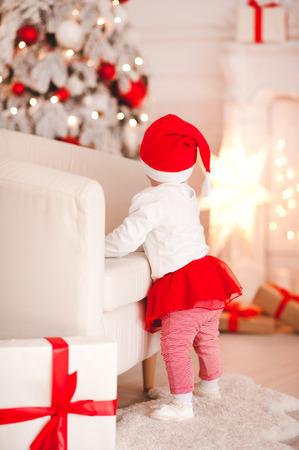 クリスマス背景にポーズのサンタ帽子をかぶって 1 歳のかわいい女の子。背面図。ホリデー シーズン。