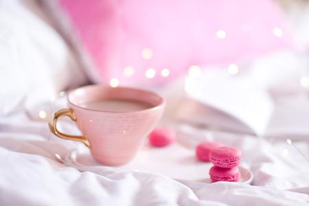 コーヒーとクッキーを使ったマグカップは、背景にライトが付いたベッドのトレイに置いてあります。おはようございます。選択的フォーカス。 写真素材 - 97532516