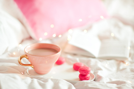 Cup of coffee with pink cookies staying in bed with open book at background. Selective focus.
