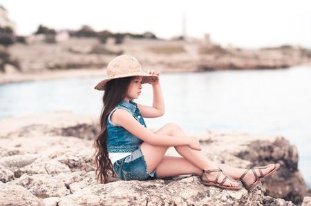 Cute kid girl 5-6 year old wearing straw hat sitting at sea shore. Looking forward. Summer season. 写真素材 - 105232578