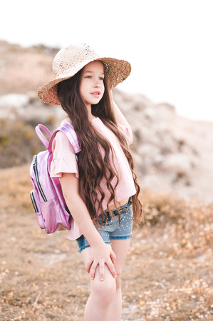 Cute kid girl 4-5 year old wearing straw hat and pink backpack outdoors. Looking forward. Summer season. 写真素材 - 105232564