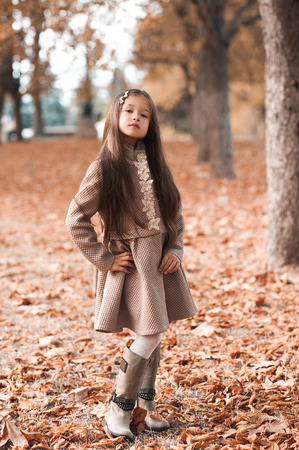 Pretty kid girl 4-5 year old wearing stylish autumn clothes in park. Looking at camera. Fall season. Childhood. 写真素材 - 105232583