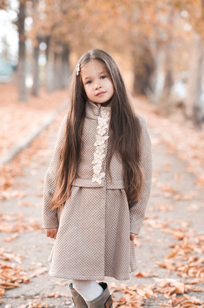 Smiling baby girl 4-5 year old wearing stylish autumn clothes in park. Looking at camera. Childhood.