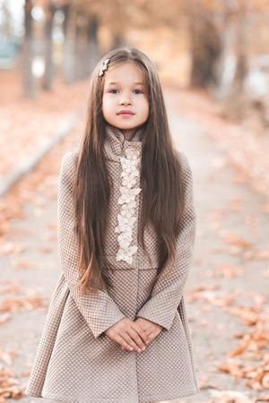 Cute kid girl 4-5 year old wearing beige jacket in park. Looking at camera. Childhood. Autumn season. 写真素材 - 105232585