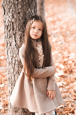Beautiful kid girl 4-5 year old wearing stylish autumn jacket in park. Looking at camera. Childhood.
