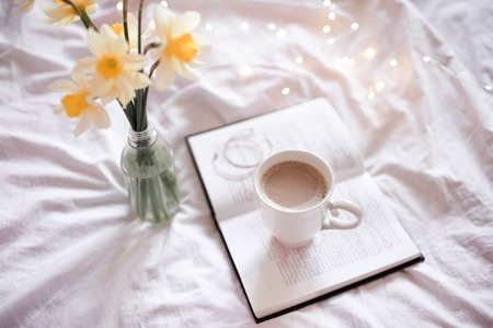 Good morning with fresh cup of coffee and reading in bed. 写真素材
