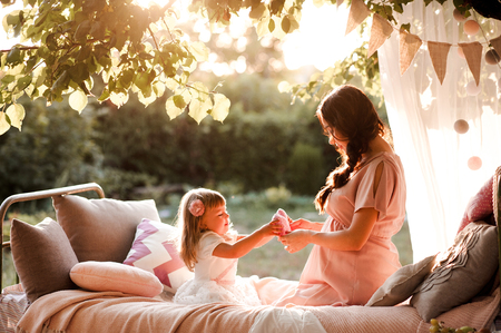 Pregnant mother playing with little child girl 3 year old outdoors. Motherhood. Maternity. 写真素材 - 118537276