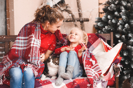 Young mother with baby girl sitting with cat over Christmas decorations outdoors. Looking at each other. Winter holidays. 写真素材 - 118537281