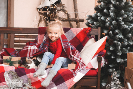 Smiling baby girl 3-4 year old sitting with cat over Christmas decor at background. Winter holidays. Childhood. 写真素材 - 118537282