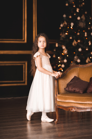 Cute baby girl 4-5 year old wearing stylish white dress posing over Christmas lights in room. Looking at camera. Holiday season.