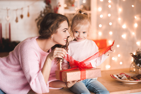 Smiling baby girl with mother open Christmas present box over lights at background. Looking at camera. Winter holiday.