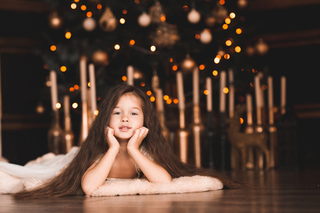 Funny baby girl 5-6 year old lying under Christmas tree  in room. Looking at camera. Winter season. 写真素材 - 118537287