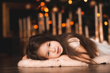Cute baby girl 4-5 year old lying on floor over Christmas lights at background. Looking at camera. Winter holidays. 写真素材 - 118537289