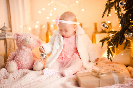 Cute baby girl 1 year old wearing princess dress playing with pink fluffy teddy bear sitting in room over Christmas lights. Holiday season.