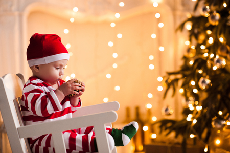 Baby 1 year old wearing santa claus suit sitting in rocking chair over Christmas tree and lights on background in room. Holiday season.