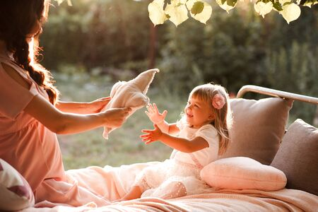 Funny baby girl playing with mother in bed over nature background closeup. Motherhood. Good morning.
