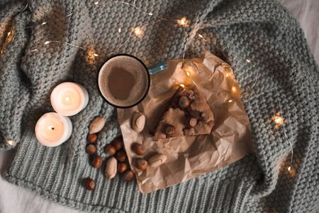 Hot chocolate with pie, nuts and burning candles over knitted sweater in lights closeup. Top view. Autumn season concept. Good morning. Breakfast. 写真素材 - 131954810