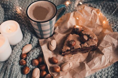 Homemade chocolate cake with nuts and cup of coffee in bed on knitted cloth close up. Good morning. Breakfast. Autumn season. Still life.