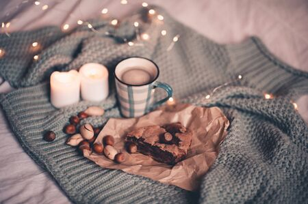 Winter concept. Cup of hot coffee with chocolate pie with nuts and burning candles over Christmas lights closeup. Winter holiday season. Good morning.  Reklamní fotografie