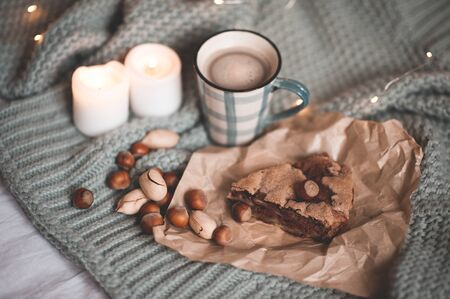 Cup of hot chocolate with tasty piece of pie, nuts and burning candles on knitted cloth closeup in bed. Top view. Good morning. Breakfast. Winter holiday season. Still life. 写真素材 - 131955511