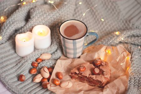 Charlotte pie with nuts, cup of coffee and burning candles in bed staying on knitted cloth close up. Good morning. Autumn season. 写真素材 - 131955947
