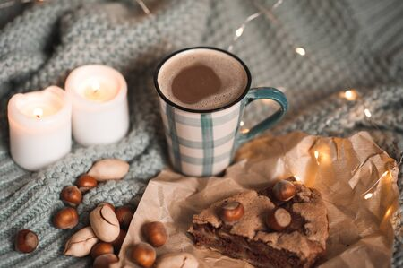 Tasty breakfast with hot cup of coffee, chocolate charlotte pie and nuts over burning cande lights at background close up. Good morning. Autumn season.  Reklamní fotografie