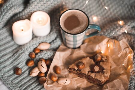 Tasty charlotte pie with nuts, cup of coffee with milk and burning candles staying on knitted cloth in bed close up. Good morning. Winter holiday season. Breakfast. 写真素材 - 131955425