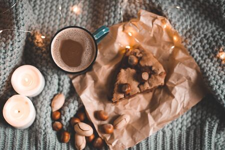 Cup of hot coffee with milk and chocolate pie, nuts and burning candles in bed on knitted blanket closeup. Top view. Good morning. Breakfast. Winter holiday season. 写真素材 - 131958246