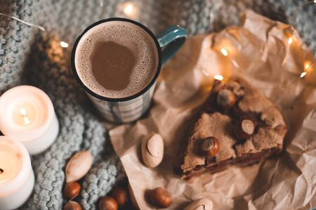 Mug of coffee with chocolate charlotte pie and nuts with burning candles in bed over lights closeup. Autumn season. Good morning. Breakfast. Still life. 写真素材 - 131954848