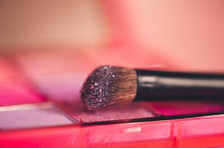 Make up brush with glitter shaows closeup. Selective focus. 写真素材 - 131958269