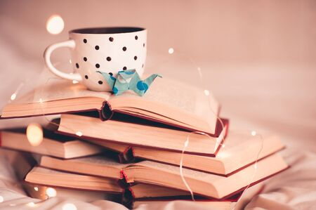 Cup of coffee with origami crane on stack of open books close up. Good morning. Education.