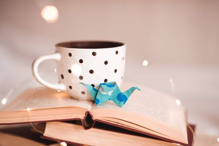 Cup of tea with paper origami crane on open books close up over lights. Good morning.