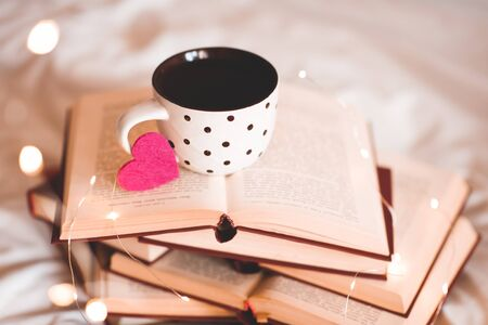 Cup of tea with pink heart on open books close up in room over lights. Winter holiday season. Valentines Day. Good morning.
