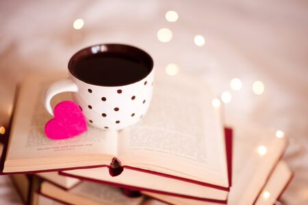 Hot coffe in cup with pink heart on open books close up over lights. Valentines Day concept. Good morning. Holiday season. 写真素材 - 131955064