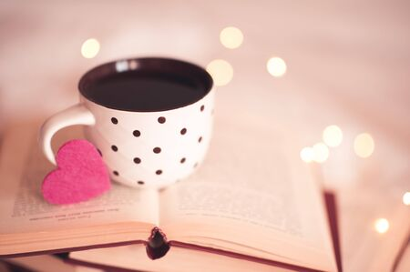 Valentines Day. Mug of tasty fresh coffee staying in open books over lights at background close up. Good morning. Holiday season.