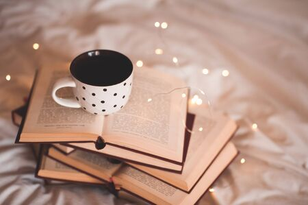 Cup of fresh black tea staying on stack of open books over Christmas lights in room close up. Winter holiday season concept. 写真素材 - 131955141