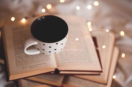Mug with fresh black tea staying on stack of open books over lights in room close up. Winter holiday season. Good night. Working at home. Freelance. Reklamní fotografie