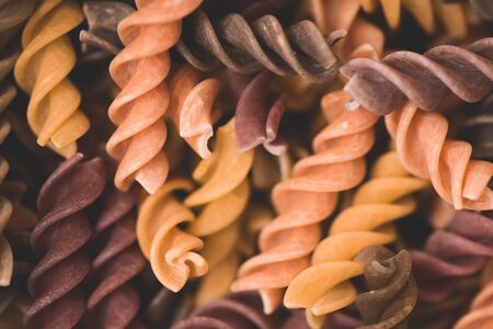 Fusilli pasta in different colors closeup. Cooking delicious dinner. Selective focus.