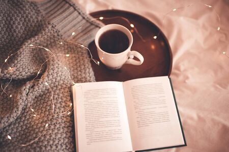 Black tea in white up with open book and knitted jersey closeup. Winter holiday season. breakfast. Good morning. Breakfast time.
