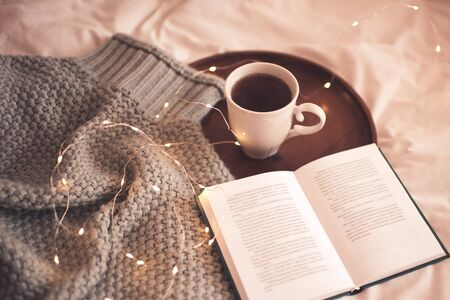 Cup of black tea and open book with knitted jersey over Christmas lights at background. Good morning. Breakfast. Winter holidays. Merry Christmas. New Year.