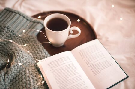 Cup of coffee with open book and woolen sweater on wooden tray in bed closeup. Breakfast time. Good morning. Winter holiday season. New Year.