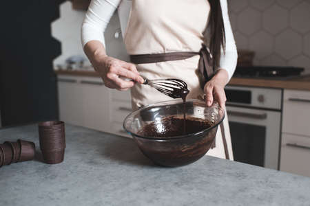 Woman making chocolate batter on table for cupcakes standing in kitchen close up. Selective focus.