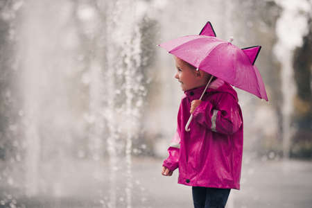 Laughing kid girl 4-5 year old holding pink umbrella wearing raincoat over rain at background closeup in park. Childhood. Autumn season.