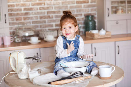 Child girl 3-4 year old sitting on kitchen table making cake with four in white bowl and mixer close up. Childhood.